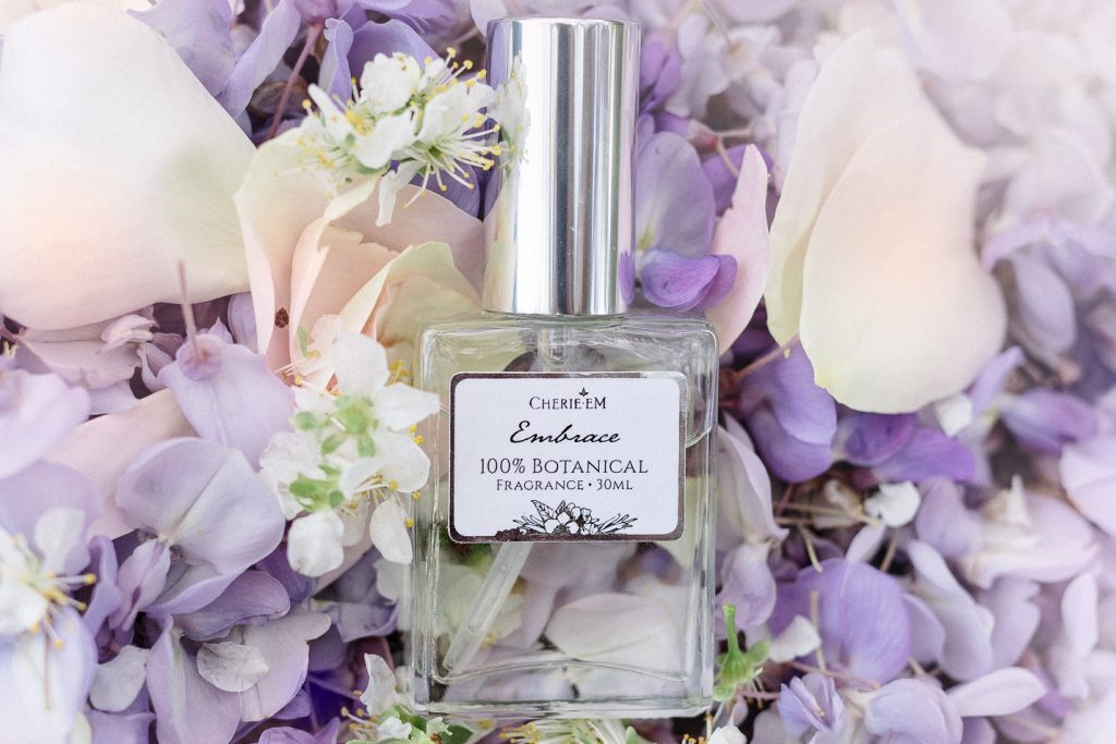 'Embrace' 30ml botanical, all natural perfume, laid on a bed of flowers.