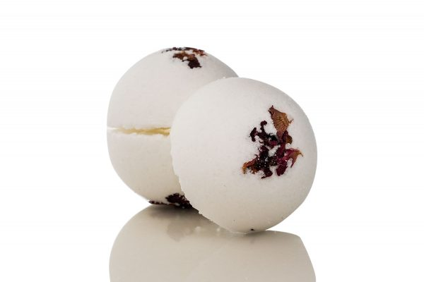 bath bomb made with rose and geranium essential oils, featuring dried rose petals on top.